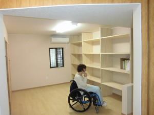 一室完成。車椅子の女性が電話をしている様子。